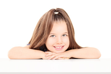Little girl sitting on table and posing