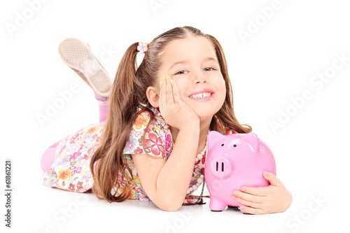 Pretty little girl laying on floor with piggybank
