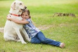 Young girl hugging pet dog at park