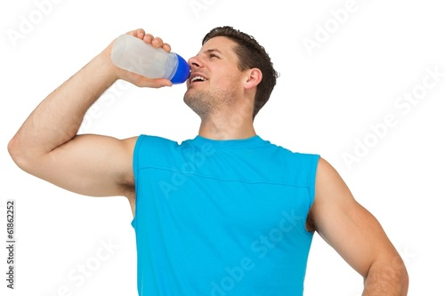 Smiling young man drinking water