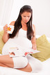 Beautiful pregnant woman drinking tea and reading magazine on so