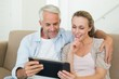 Happy couple using tablet pc together on the couch