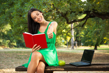 Beautiful female student with toothy smile holding book and show