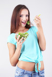 Beautiful girl with fresh salad on grey background