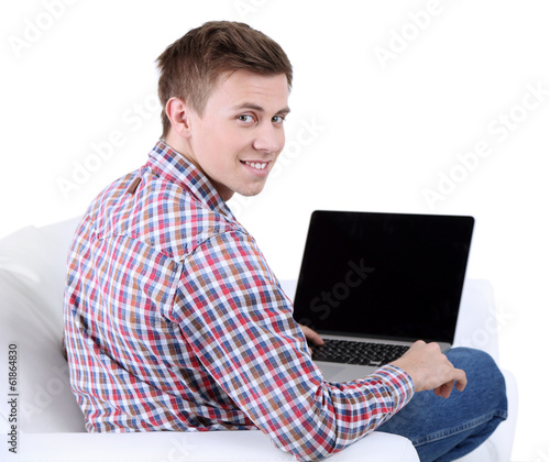 Guy sitting on sofa with laptop on white background