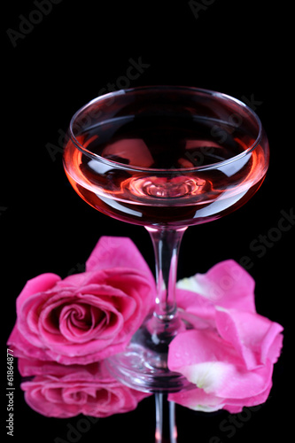 Composition with pink sparkle wine in glass and  rose isolated