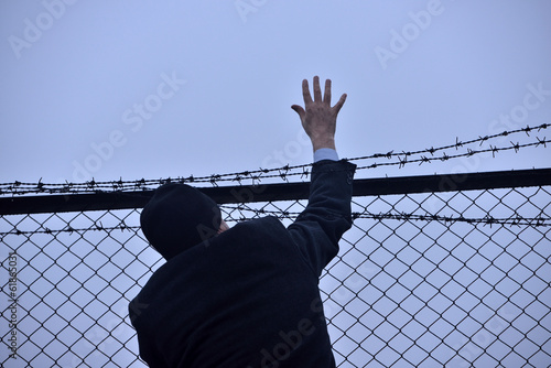 man extends his hand out of the barbed wire