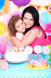 Pretty little girl with mom celebrate her birthday