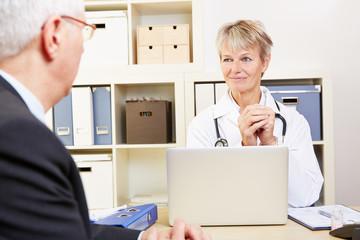 Ärztin im Gespräch mit Patient in Sprechstunde