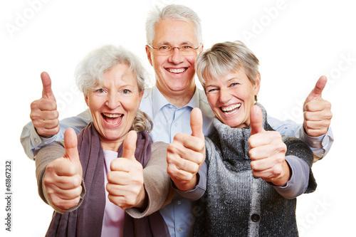 canvas print picture Drei Senioren halten glücklich Daumen hoch