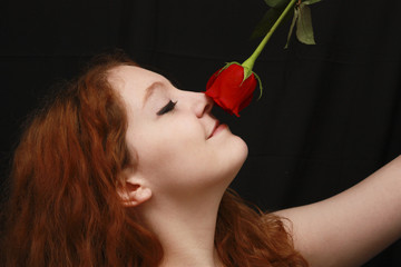 Young woman with her head tipped back smelling red rose