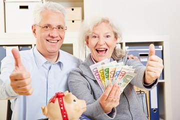 Senioren mit Geld halten Daumen hoch