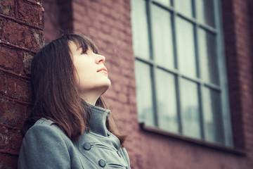 pensive beautiful young girl standing near a brick wall