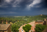 Houses and trees in Provence, with dark, stormy sky
