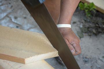 carpenter cutting a slat of wood using a saw