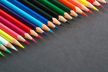 Colorful pencils in a row on a dark background