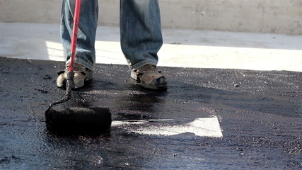 Road men manually applying asphalt on the highway