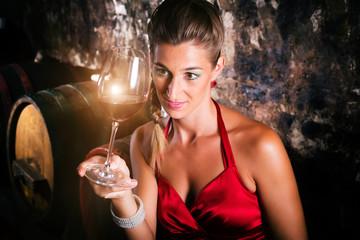 Frau in Weinkeller mit Wein bei Weinprobe