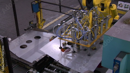 Robotic Arms Moving Sheet Metal Along Assembly Line