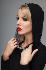 Beautiful blonde wearing an black hoodie on a gray background