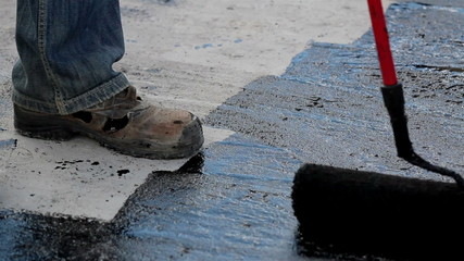 Road men applying asphalt using a roller brush