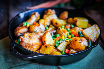 Oven baked chicken with potatoes and vegetables on wooden backgr