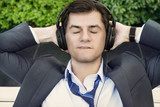 Businessman is relaxing in headphones with closed eyes on the be