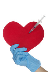 Hand in blue glove holding heart with syringe