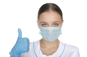 Doctor in blue gloves and mask raised thumb