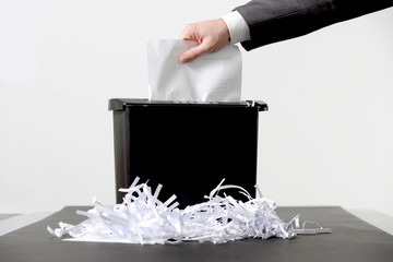 Hand of businessman putting a document in paper shredder
