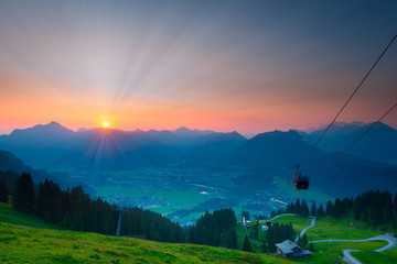 sunbeams while sunrise in austrian mountains with ropeway