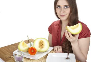 Junge Frau isst eine Galiamelone