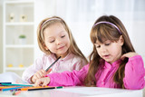 Two cute little girls drawing with colored pencils