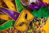 Colorful group of Mardi Gras or venetian masks on yellow