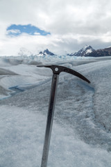 Ice axe fixed in the snow with a glacier landscape background
