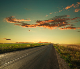 Lonely road leading to the horizon at sunset sky background