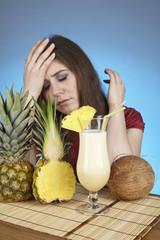 Junge Frau mit Pina-Colada, Ananas und Kokosnuss am Esstisch