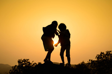 Boy and girl are climbing the hill during sun set.
