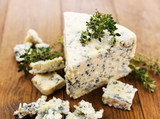 Tasty blue cheese with thyme, on wooden table