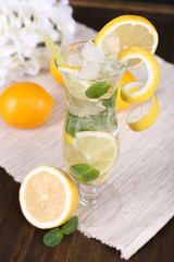 Glass of cocktail with lemon and mint on table close-up