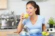 Girl drinking orange juice eating breakfast