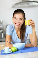 Woman drinking orange juice eating breakfast