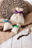 Sacks with coffee on wooden table, on sackcloth background