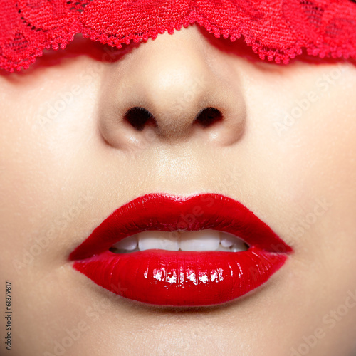 close-up shot of woman with red lacy ribbon on eyes