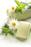 green soap and towel with herb on background