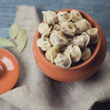Boiled pelmeni in a ceramic pot, view from above