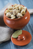 Ceramic pot with boiled pelmeni, vertical shot