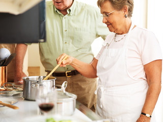 elderly married couple cooking food in the kitchen