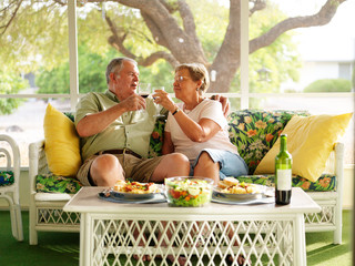 elderly couple drinking wine with their dinner