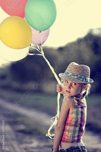 Girl with balloons in a summer warm day